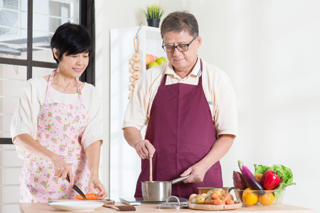 Asian senior couple preparing meal at kitchen.