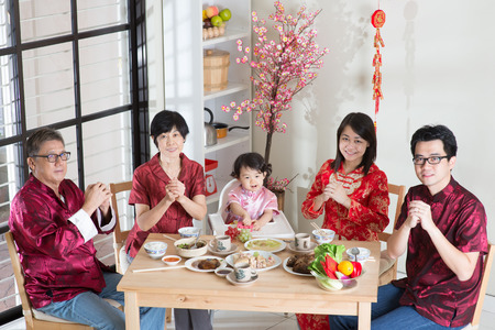 traditional celebrations: Happy Chinese New Year, reunion dinner. Happy Asian Chinese multi generation family with red cheongsam greeting while dining at home.