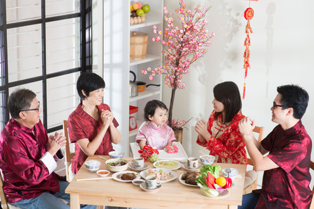 chinese new year food:   Happy Asian Chinese multi generation family with red cheongsam dining at home.