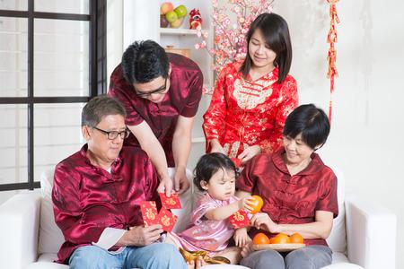 Gelukkig Aziatische meerdere generaties familie in het rood cheongsam met rode pakjes terwijl reünie thuis.