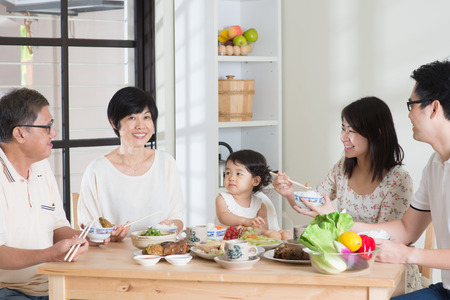 comiendo: Asi�ticos m�ltiples generaciones chinas felices de la familia a cenar en su casa. Foto de archivo