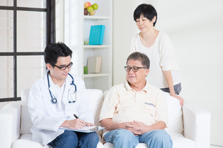 Doctor and patient. Asian senior couple consult family doctor, sitting on sofa. Senior retiree indoors living lifestyle.