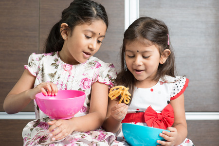 murkoo: Two cute Indian girls eating traditional snack murukku.  Stock Photo