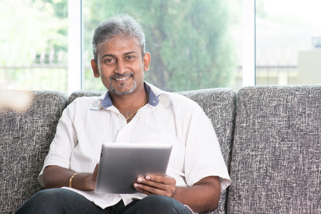 using tablet:  Mature Indian man using touch screen tablet computer at home.