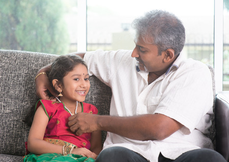 single family house: Indian father dressing daughter at home, preparing for diwali.  Stock Photo