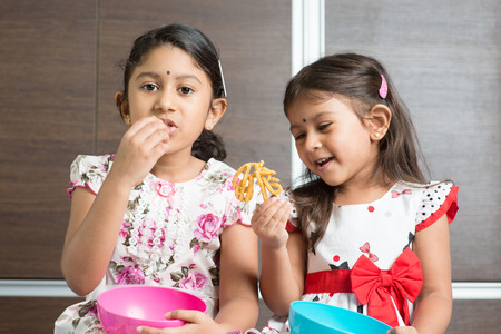 murkoo: Two cute Indian girls eating food. Asian sibling or children enjoying traditional snack murukku, living lifestyle at home.
