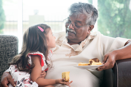 adult indian:  Grandparent and grandchild eating butter cake. Asian people living lifestyle.