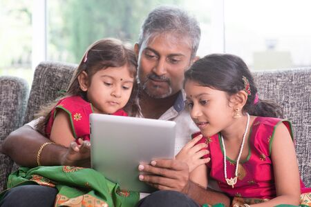 home schooling:   Asian father and children using touch screen tablet computer, sitting on sofa, home schooling concept. Stock Photo