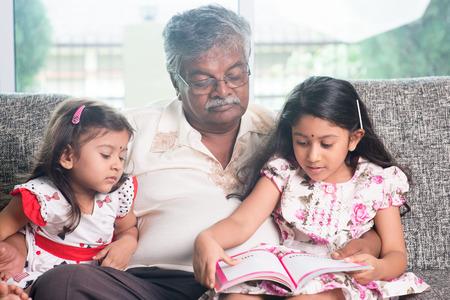 grandparent: Grandparent and grandchildren reading story book.   Stock Photo