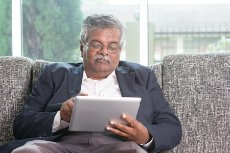 Old Indian man using touch screen tablet computer at home.