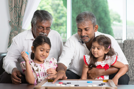 family with grandparents: Happy multi generations Asian Indian family playing carrom game at home.  Stock Photo