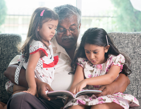 grandchildren: Asian grandfather and granddaughters reading story book. Happy Indian family at home. Grandparent and grandchildren indoor lifestyle.