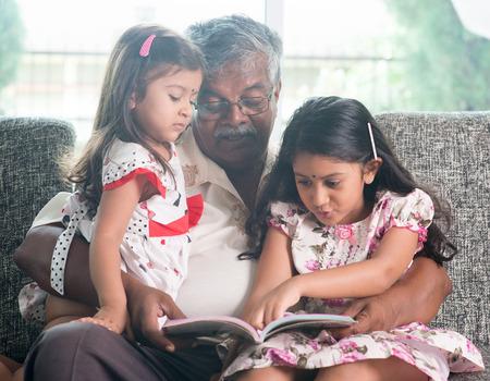 Aziatische grootvader en kleindochters lezen verhaal boek. Gelukkige Indische familie thuis. Grootouder en kleinkinderen indoor levensstijl. Stockfoto