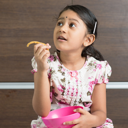 murkoo: Cute Indian girl eating traditional snack murukku.  Stock Photo
