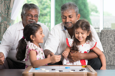 ndian family playing carom game at home.