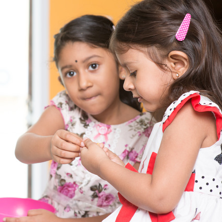 muruku: Indian girls sharing traditional snack   with each other.  Stock Photo