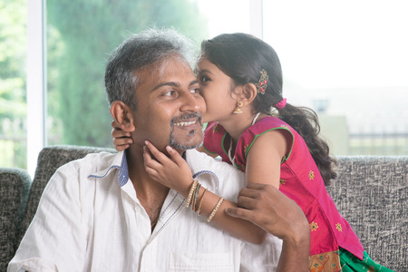 indian sweet: Indian daughter kissing father at home.  Stock Photo