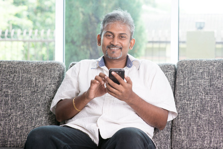 Smartphone social network concept. Indian mature guy using mobile phone. Asian man relaxed and sitting on sofa indoor.