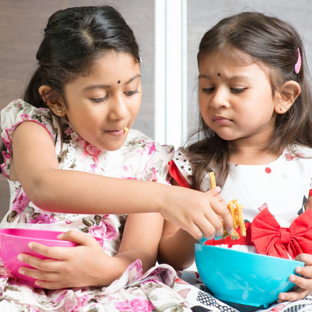 murkoo: Indian girls sharing food, traditional snack murukku with each other. Asian sibling or children living lifestyle at home.