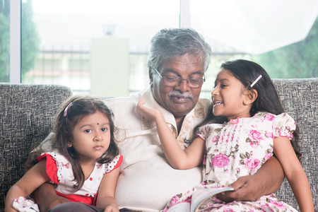 Grandparent and grandchildren reading story book together.