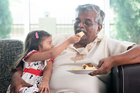 mature old generation:  randchild feeding butter cake to grandparent.   Stock Photo