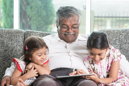 family with grandparents:  Grandparent and grandchildren using touch screen tablet computer.