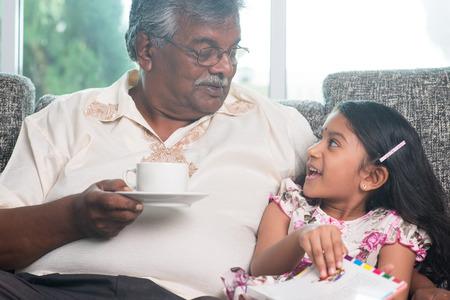 kid book: Grandparent and grandchild reading book together.