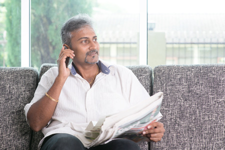 person reading: Portrait of mature Indian man calling using smart phone while reading on newspaper, sitting on sofa at home.