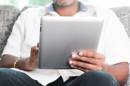 tab:  ature Indian man using touch screen digital tablet computer at home.   Stock Photo