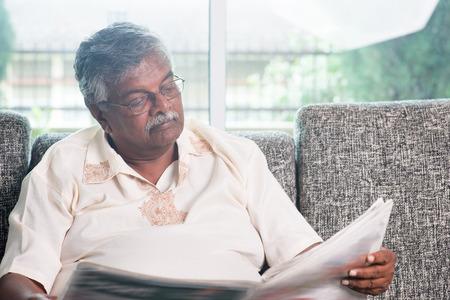 oude krant: Hogere Indische man het lezen van de krant thuis. Aziatische oude mensen wonen levensstijl binnenshuis.
