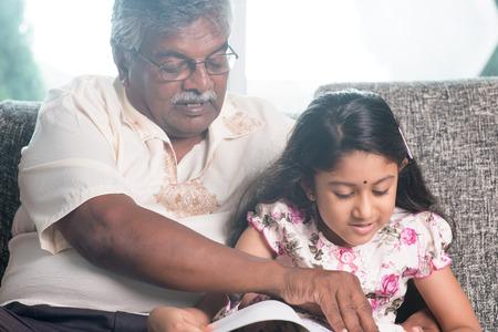 grandparent: Grandparent and grandchild reading story book together.