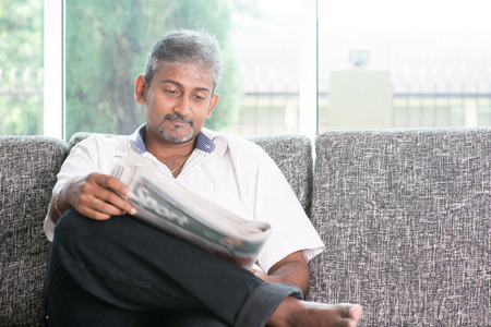 one mid adult man: Portrait of mature Indian man reading on newspaper  Stock Photo