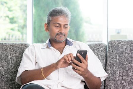 seated man: Chico madura indio que usa el teléfono móvil. Hombre asiático relajado y sentado en el sofá de interior.