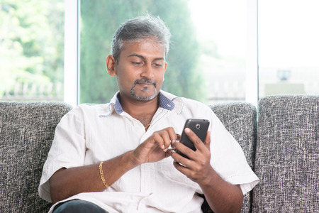 man relax:  Indian mature guy using mobile phone. Asian man relaxed and sitting on sofa indoor.  Stock Photo
