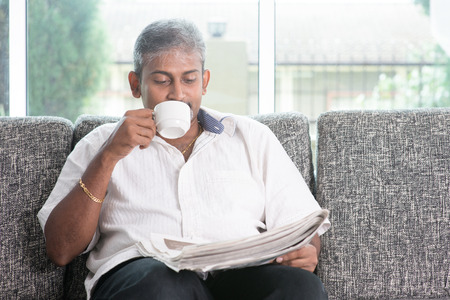old people: Portrait of mature Indian man drinking milk tea while reading on newspaper, sitting on sofa at home. Asian male relax on couch in house with interior.