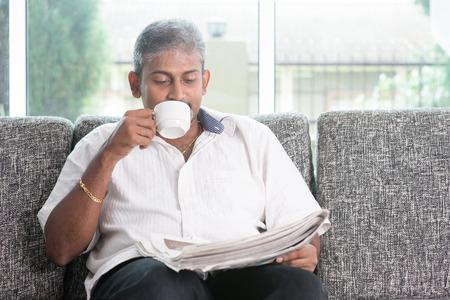 Portret van volwassen Indiase man melk drinken thee bij het lezen van de krant, zittend op de bank thuis. Aziatische mannelijke ontspannen op de bank in huis met interieur.