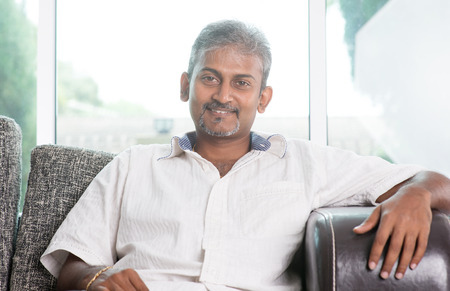 Portrait of mature Indian man sitting on sofa at home
