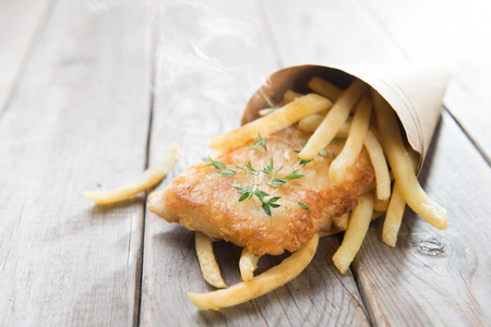 in the chips: Fish and chips. Fried fish fillet with french fries wrapped by paper cone, on wooden background.