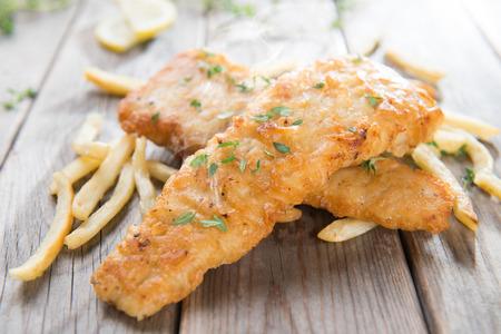 fish and chips: Pescado y papas fritas. Filete de pescado frito con patatas fritas en fondo de madera vieja. Frescos cocinados con los vapores calientes.