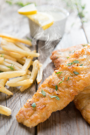 fish and chips: Fish and chips. Fried fish fillet with french fries on wooden background. Fresh cooked with hot steams. Foto de archivo