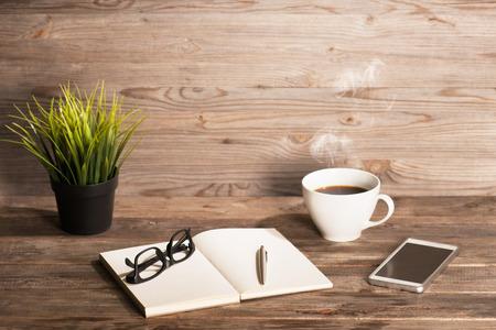 メモ帳、コーヒー カップ、ペン、スマート フォン、メガネ、植木鉢を持つ作業テーブル。木製のテーブル背景上にコピー スペースを持つ。インス