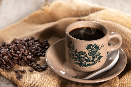 kopitiam: Steaming traditional oriental Chinese kopitiam style dark coffee in vintage mug and saucer with coffee beans. Fractal on the cup is generic print. Soft focus setting with dramatic ambient light on dark wooden background.