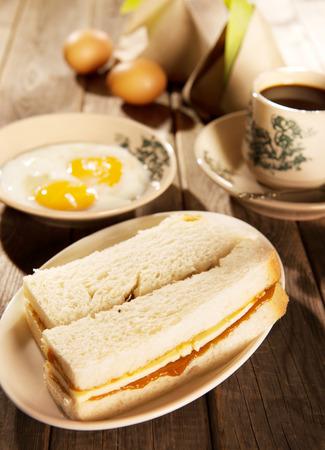 Traditionele Maleisische stijl ontbijt, kaya boter toast, nasi lemak en gekookte eieren met koffie. Fractal op de beker is generiek druk. Soft focus instelling met dramatische omgevingslicht op donkere houten achtergrond. Stockfoto