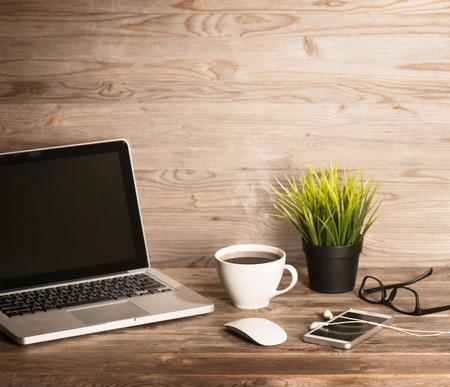 Houten kantoor interieur, een tafel met laptop, een kop hete koffie, muis, glazen, smartphone, oortelefoons en potplanten, in dramatische licht vintage afgezwakt.