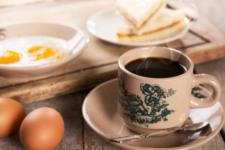 kopitiam: Traditional Singaporean Chinese style coffee in vintage mug and saucer with breakfast. Fractal on the cup is generic print. Soft focus dramatic ambient light over wood table. Stock Photo