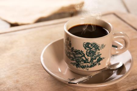 Stomen traditionele kopitiam stijl Maleisische koffie in vintage mok en schotel. Fractal op de beker is generiek druk. Soft focus instelling met dramatische omgevingslicht op donkere houten achtergrond. Stockfoto