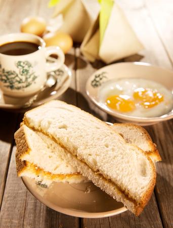 Traditionele Chinese Maleisische stijl ontbijt, kaya boter toast, nasi lemak en gekookte eieren met koffie. Fractal op de beker is generiek druk. Soft focus instelling met dramatische omgevingslicht op donkere houten achtergrond.
