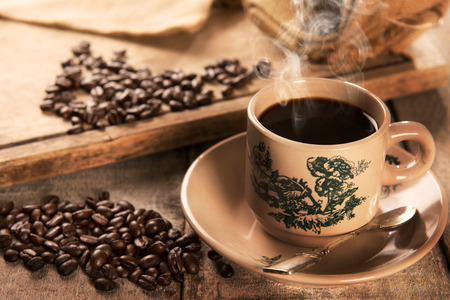 Steaming traditional Chinese style dark coffee in vintage mug and saucer with coffee beans. Fractal on the cup is generic print. Soft focus setting with dramatic ambient light on dark wooden background.