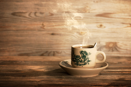 Steaming traditional oriental Chinese coffee in vintage cup and saucer.  Fractal on the cup is generic print. Soft focus setting with dramatic ambient light on dark wooden background.