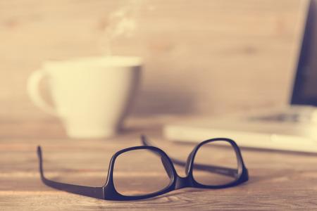 anteojos: Mesa de trabajo de madera con vidrios, ordenador port�til, una taza de caf� caliente, en dram�tico vendimia luz entonado.